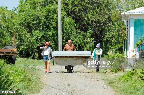 Rural scene of people transporting a mattress on a wheelbarrow over a dirt street