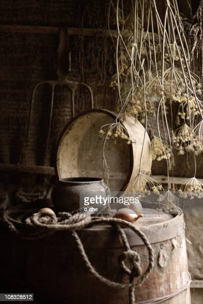 rural stil life with sieve, pot and barrel in sepia - frische stockfoto's en -beelden