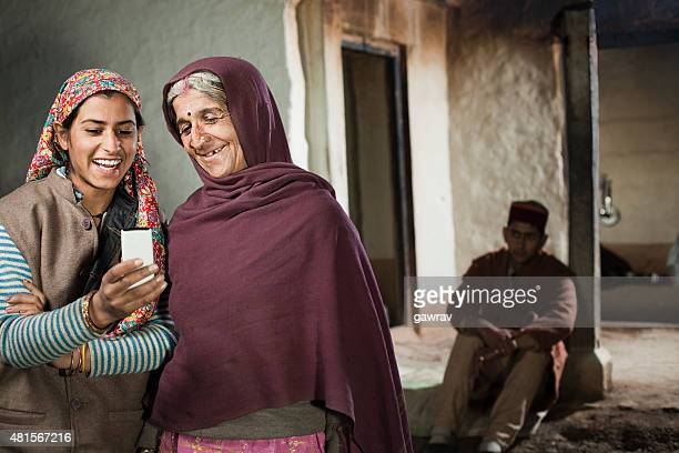 Rural teenage happy girl showing mobile phone to her grandmother.