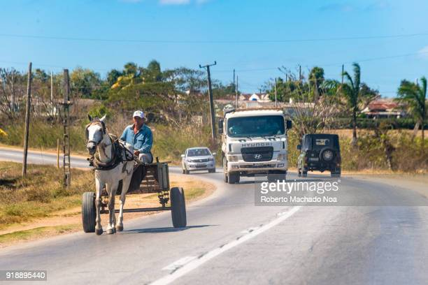 Rural traffic scene horsedrawn carriage interacts with a truck and other vehicles during the day