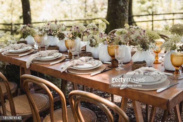 rural wedding reception in the forest with wooden table and colored glasses and floral decoration - decoration stock pictures, royalty-free photos & images