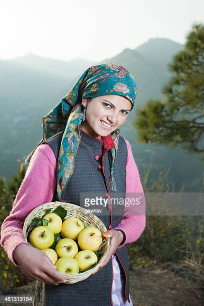 Rural woman holding apple basket looking at camera in mountains.