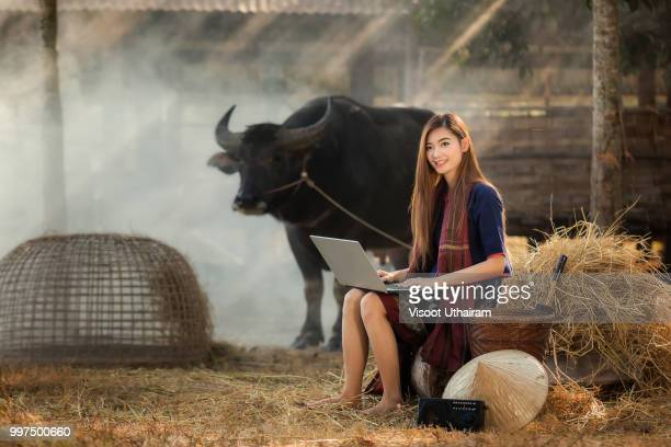 Rural woman playing computer notebook on her farm background in the countryside