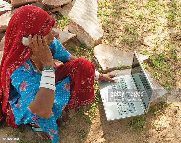 Rural woman talking on a mobile phone and using a laptop, Jaipur, Rajasthan, India.