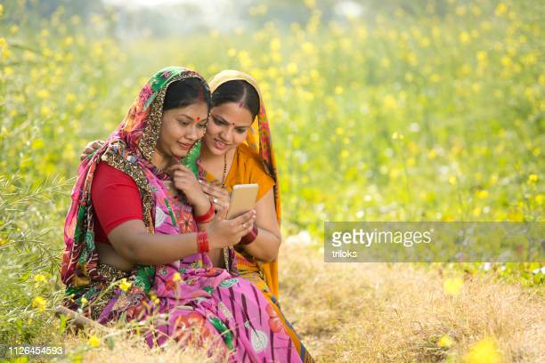 rural women using mobile phone in agricultural field - village stock pictures, royalty-free photos & images