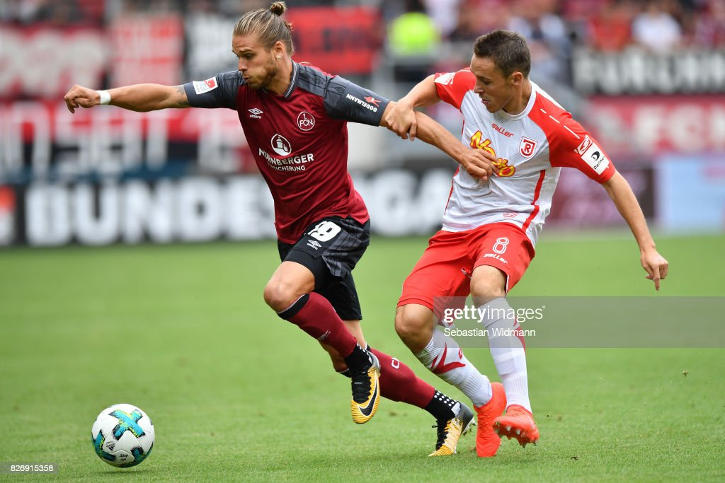 Rurik Gislason of 1. FC Nuernberg and Andreas Geipl of SSV Jahn Regensburg compete for the ball during the Second Bundesliga match between SSV Jahn Regensburg and 1. FC Nuernberg at Continental Arena on August 6, 2017 in Regensburg, Germany.