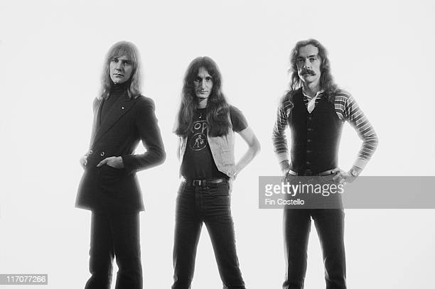 guitarist Alex Lifeson bassist and singer Geddy Lee and drummer Neil Peart Canadian rock band pose against a white background for a group studio...