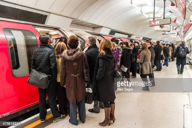 Rush hour commuters trying to board overcrowded London Underground train UK