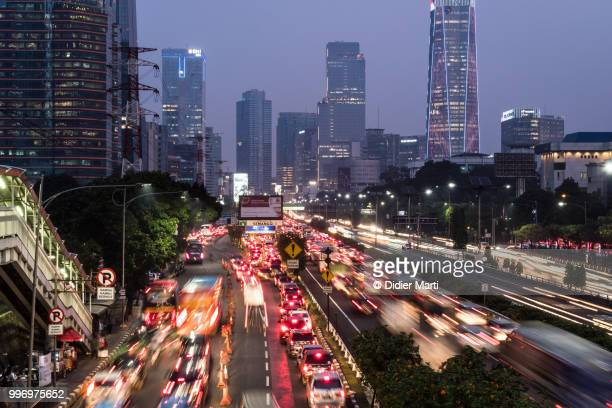 Rush hour traffic captured with long exposure along the Gatot Subroto highway in the heart of Jakarta business district in Indonesia