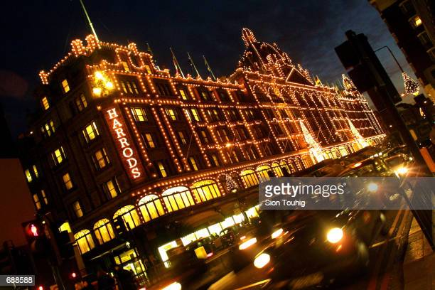 Rush hour traffic drives past Harrods department store dressed for the holidays December 20 2001 in Knightsbridge in London The store is...