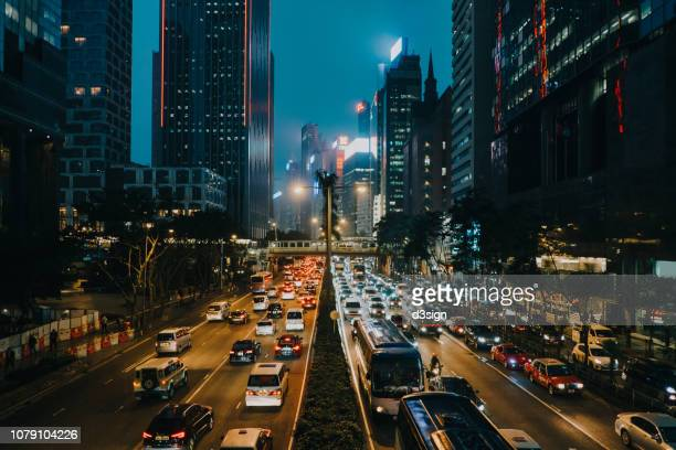 rush hour traffic on busy highway in downtown financial area in the evening - urban sprawl stock pictures, royalty-free photos & images