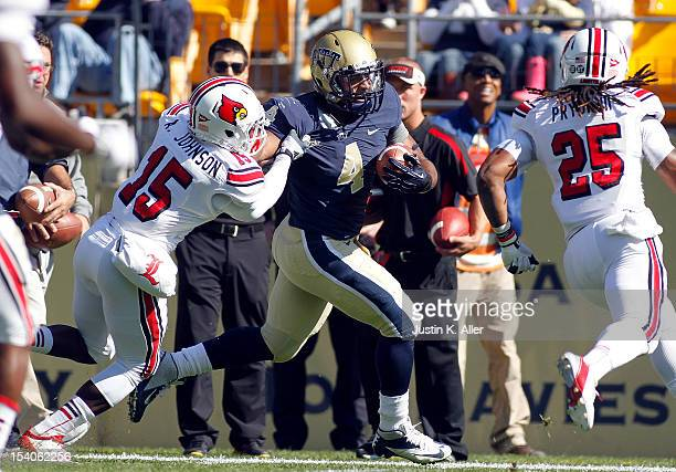 Rushel Shell of the Pittsburgh Panthers carries the ball against Andrew Johnson of the Louisville Cardinals during the game on October 13 2012 at...
