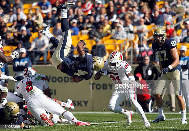 Rushel Shell of the Pittsburgh Panthers rushes for a twoyard touchdown against Adrian Bushell of the Louisville Cardinals in the second quarter...