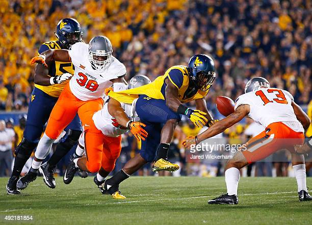 Rushel Shell of the West Virginia Mountaineers fumbles the ball before it is recovered by Jordan Sterns of the Oklahoma State Cowboys in the first...