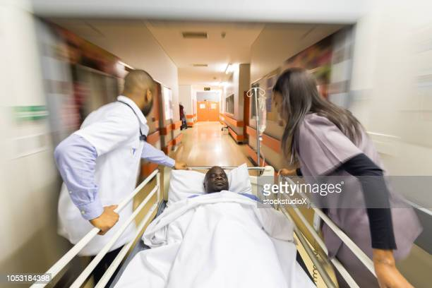 rushing a patient to the emergency room - emergency room stock pictures, royalty-free photos & images