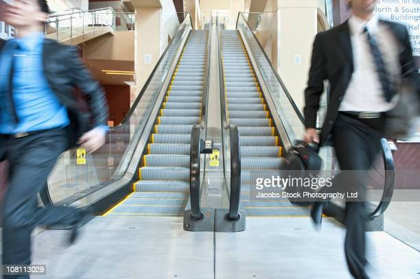 rushing businessmen running off escalator - sells arizona stock pictures, royalty-free photos & images
