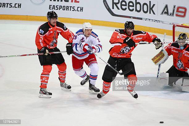 Ruslan Fedotenko of the New York Rangers pursues the puck between Chiesa Alessandro and Andy Wozniewski of EV Zug at the Bossard Arena during the...