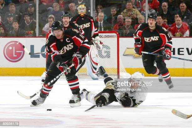 Ruslan Fedotenko of the Pittsburgh Penguins dives to stick-check the puck from Daniel Alfredsson of the Ottawa Senatorsm at Scotiabank Place on...
