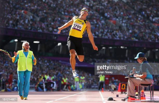 Ruslan Katyshev of Ukraine is watched by his guide as he competes in the Men's Long Jump - F11 Final on day 6 of the London 2012 Paralympic Games at...