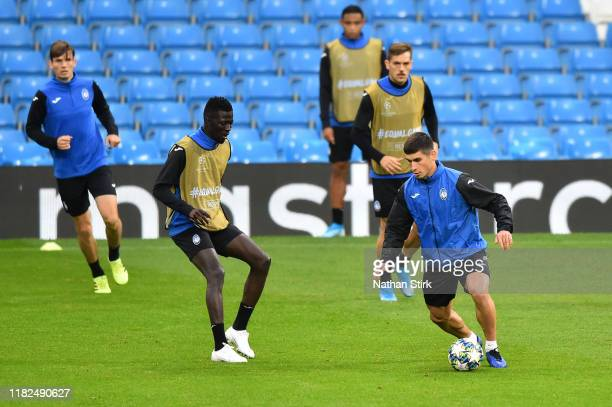 Ruslan Malinovskyi and Musa Barrow of Atalanta take part in a training session ahead of the UEFA Champions League Group C match against Manchester...