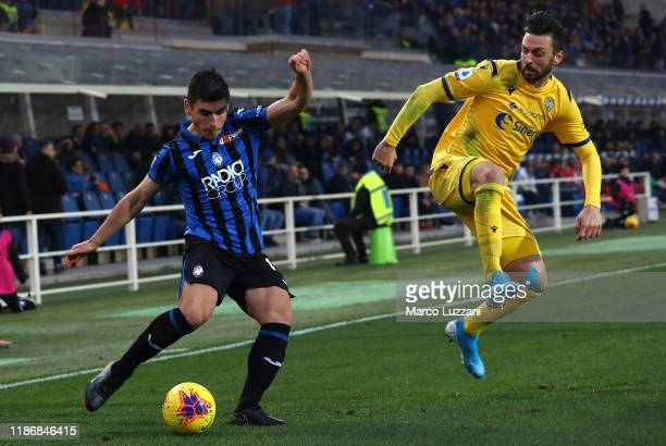 Ruslan Malinovskyi of Atalanta BC competes for the ball with Samuel Di Carmine of Hellas Verona during the Serie A match between Atalanta BC and...