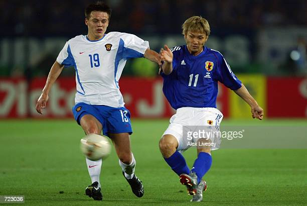 Ruslan Pimenov of Russia tries to tackle Takayuki Suzuki of Japan during the FIFA World Cup Finals 2002 Group H match played at the International...