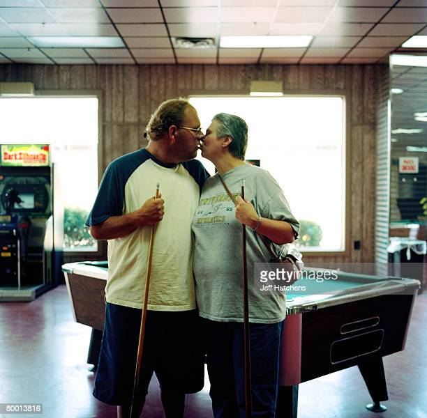 Russ Corbett and Georgia Bailey lock lips on a brief vacation while playing a game of pool and posing for a portrait in an arcade at South of the...