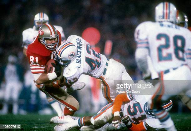 Russ Francis of the San Francisco 49ers is tackled by Lyle Blackwood of the Miami Dolphins during Super Bowl XIX on January 20 1985 at Stanford...