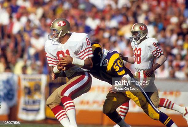 Russ Francis of the San Francisco 49ers tries to avoid the tackle of Jim Collins of the Los Angeles Rams during an NFL football game at Anaheim...