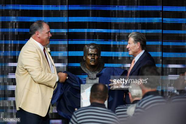 Russ Grimm and presenter Joe Bugel unveil Grimm's bust during the 2010 Pro Football Hall of Fame Enshrinement Ceremony at the Pro Football Hall of...