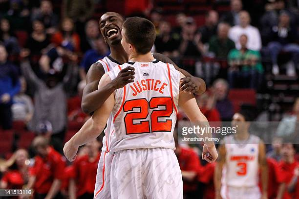 Russ Smith and Elisha Justice of the Louisville Cardinals celebrate the Cardinals 59-56 victory against the New Mexico Lobos during the third round...