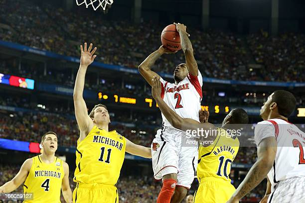 Russ Smith of the Louisville Cardinals drives for a shot attempt in the first half against Nik Stauskas and Tim Hardaway Jr #10 of the Michigan...