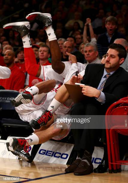 Russ Smith of the Louisville Cardinals falls over a teammate on the bench out of bounds in the first half against the Syracuse Orange during the...