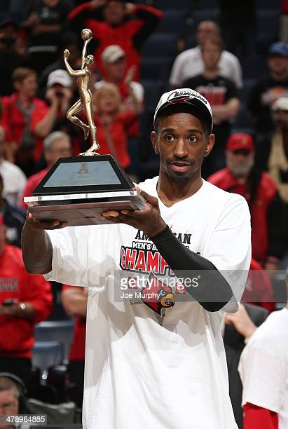 Russ Smith of the Louisville Cardinals holds up the MVP tournament trophy after defeating the Connecticut Huskies during the Championship of the...