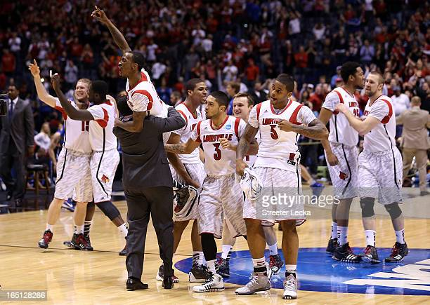 Russ Smith of the Louisville Cardinals is held up by assistant coach Kevin Keatts as they celebrate with teammates after they won 8563 against the...