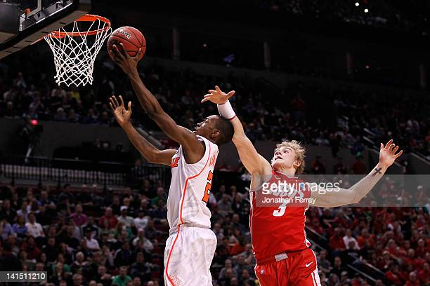 Russ Smith of the Louisville Cardinals lays the ball up in front of Hugh Greenwood of the New Mexico Lobos in the second half during the third round...