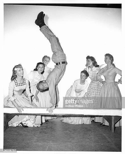 Russ Tamblyn on the balance beam as Ruta Kilmonis Betty Carr Nancy Kilgas Virginia Gibson Julie Newmeyer and Norma Doggett watches him in a scene...