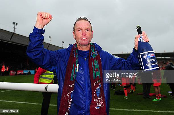 Russ Wilcox Manager of Scunthorpe United celebrates his side's promotion to League One after the Sky Bet League Two match between Exeter City and...