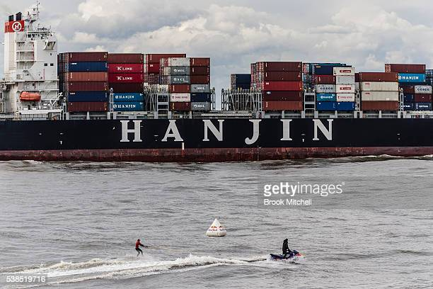 Russell Bierke tows out to catch a wave as a container ships heads out of Botany Bay during Cape Fear on June 7, 2016 in Sydney, Australia.