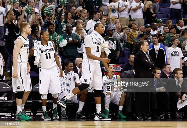 Russell Byrd Keith Appling Adreian Payne and Travis Trice of the Michigan State Spartans celebrate on the bench as head coach Tom Izzo of the...