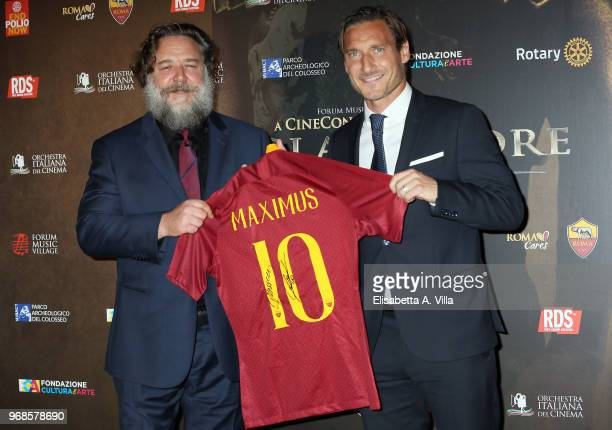 Russell Crowe receives a special AS Roma Football team's jersey from Francesco Totti as they attend the 'Il Gladiatore In Concerto' charity night at...