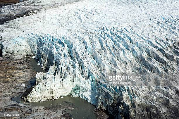 Pressure ridges and crevasse scar the surface of a glacier on the Greenland Ice Sheet.