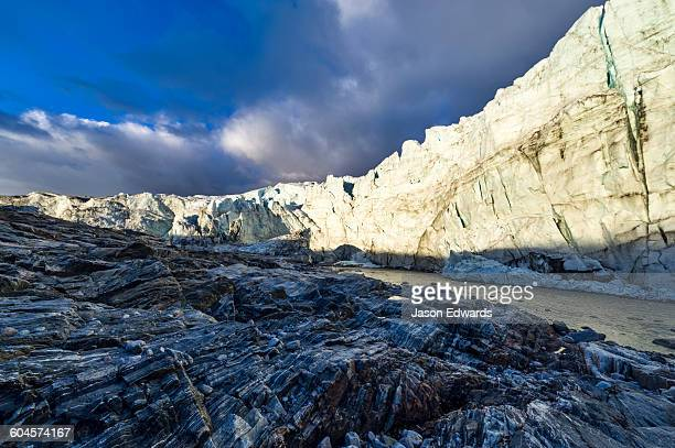 the setting sun illuminates the sheer ice cliff of a glacier fracture zone with a river at its base. - gneiss stock pictures, royalty-free photos & images