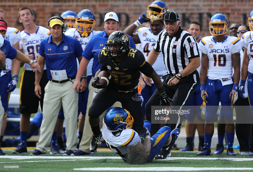 Russell Hansbrough #32 of the Missouri Tigers is tackled by T.J. Lally #33 of the South Dakota State Jackrabbits in the first quarter at Memorial Stadium on August 30, 2014 in Columbia, Missouri.