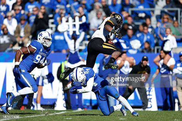 Russell Hansbrough of the Missouri Tigers jumps over Blake McClain of the Kentucky Wildcats during first half action at Commonwealth Stadium on...