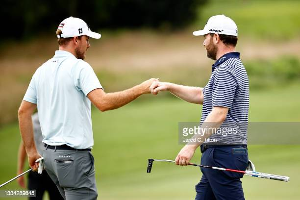 Russell Henley of the United States fist bumps Branden Grace of South Africa after Grace make a birdie putt on the seventh green during the final...