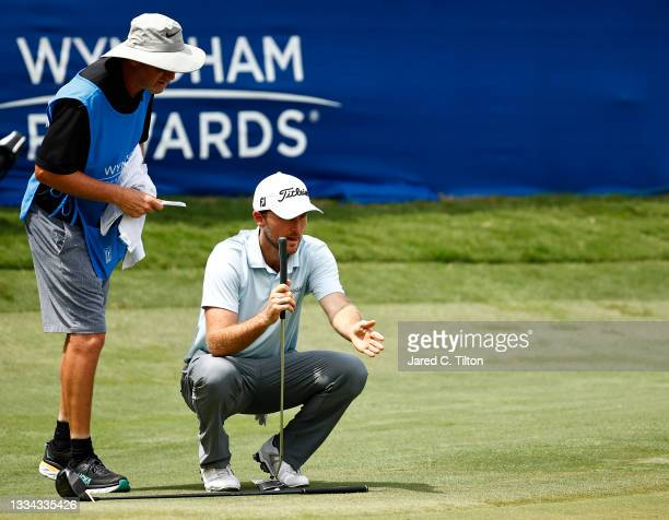 Russell Henley of the United States talks with caddie Todd Gjesvold before putting on the 18th green during the final round of the Wyndham...