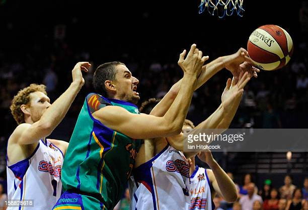 Russell Hinder of the Crocodiles contests the ball with Stephen Weigh of the 36ers during the round 12 NBL match between the Townsville Crocodiles...