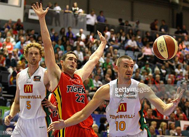 Russell Hinder of the Crocodiles gathers a loose ball during the round 24 NBL match between the Melbourne Tigers and the Townsville Crocodiles at...
