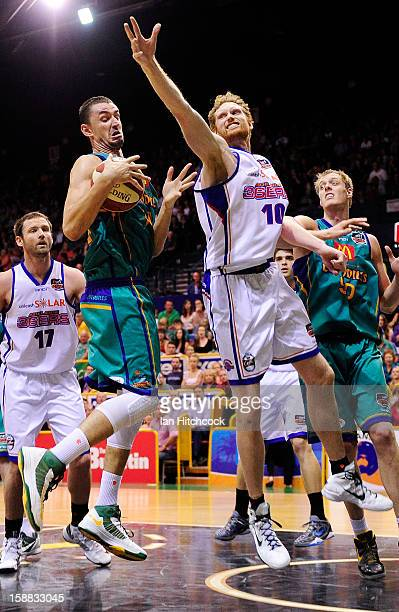 Russell Hinder of the Crocodiles gathers a rebound past Luke Schenscher of the 36ers during the round 12 NBL match between the Townsville Crocodiles...